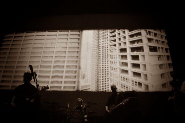 Bandmitglieder von Godspeed You! Black Emperor vor einer Filmprojektion während ihres Konzerts in Dresden